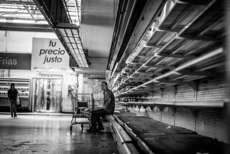 poza alb-negru supermarket rafturi goale cumparator venezuela