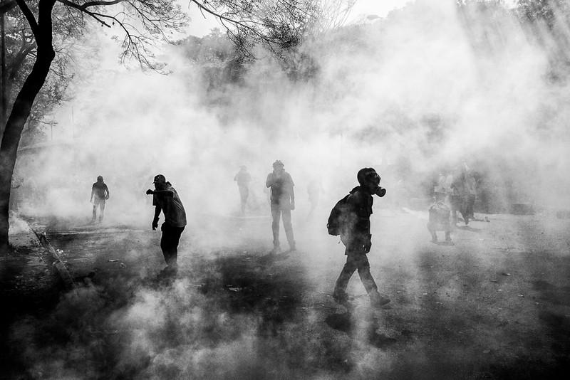 poza alb-negru demonstrantii masca gaze lacrimogene