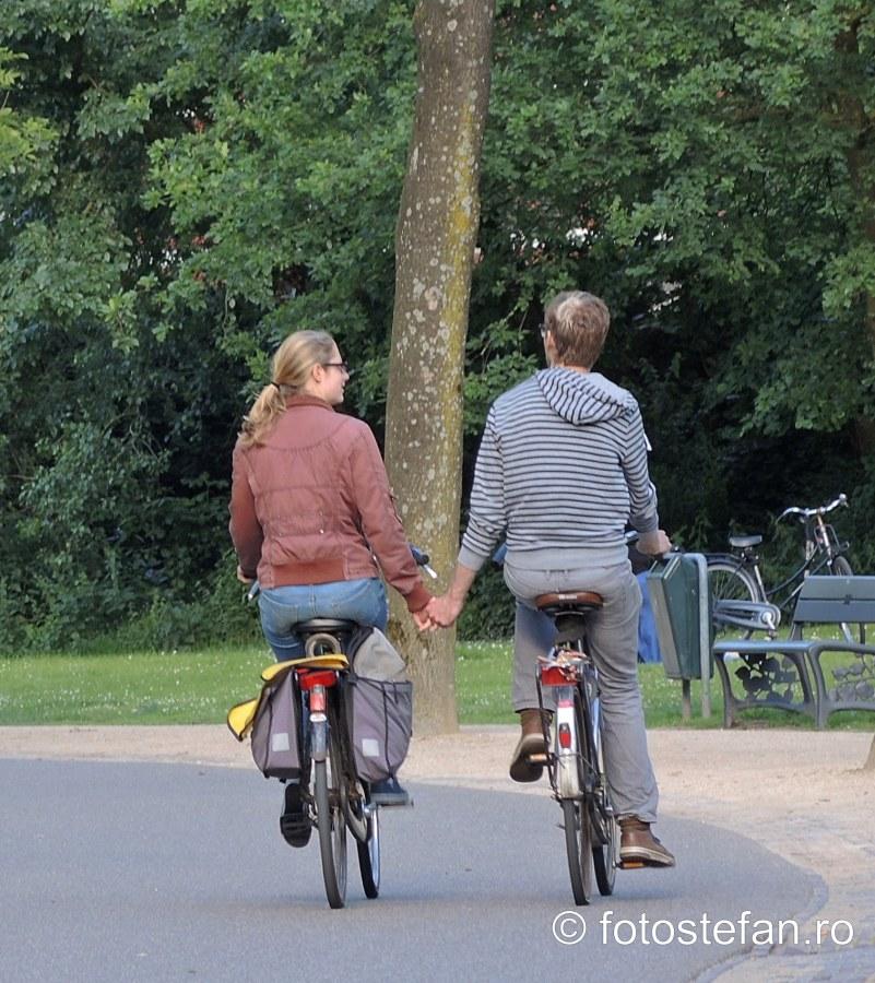 poza biciclisti tinindu-se de mina cuplu baiat fata foto
