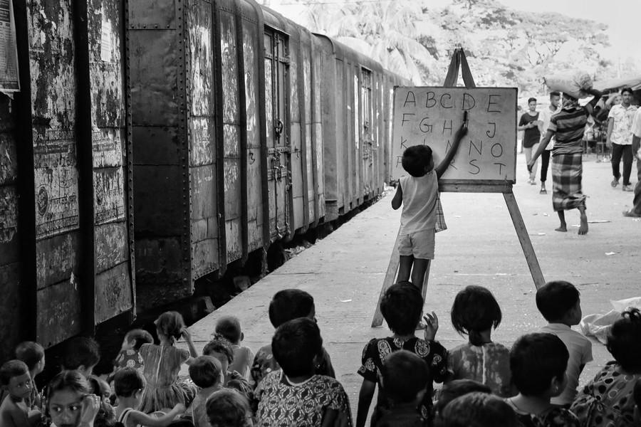 poza alb negru copii invatand scoala afara tren